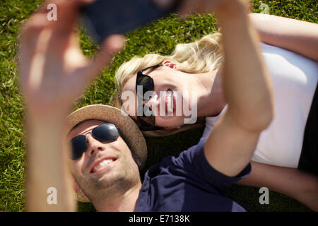 Couple lying in park taking selfie on smartphone - Stock Photo