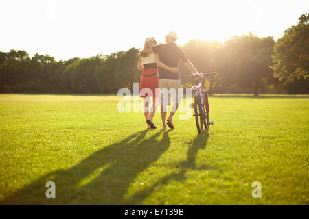 Couple strolling whilst pushing bicycle in park