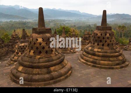 Borobudur, Java, Indonesia.  Stupas on Upper Terrace of the Temple Awaiting Sunrise.  The diamond-shaped holes symbolize - Stock Photo