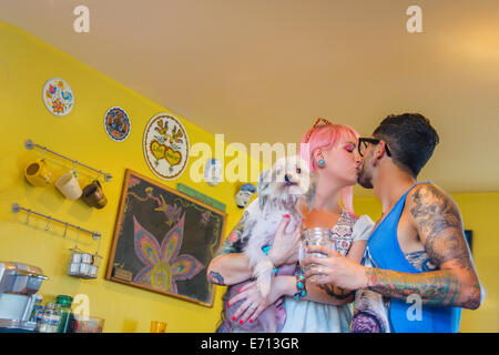 Couple kissing in kitchen whilst carrying pet dog - Stock Photo