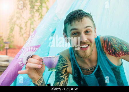 Portrait of young man with teacup in tent - Stock Photo