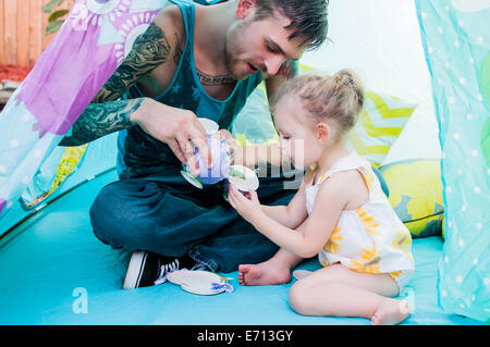Young man and toddler daughter playing with teacup in tent - Stock Photo