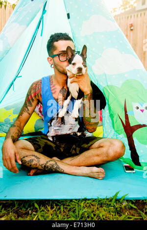 Portrait of funky man holding up his pet dog - Stock Photo