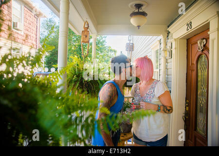 Funky couple kissing on porch - Stock Photo