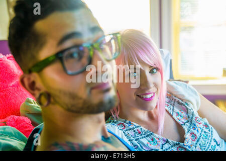 Portrait of funky couple reclining on bed - Stock Photo