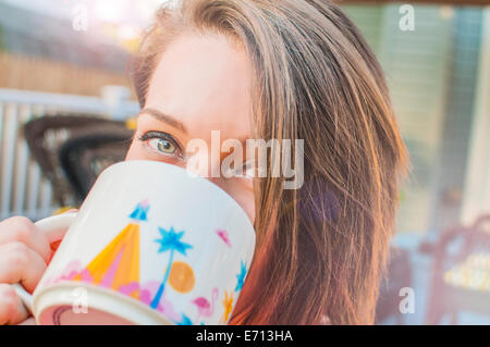 Close up of young woman drinking coffee from mug - Stock Photo