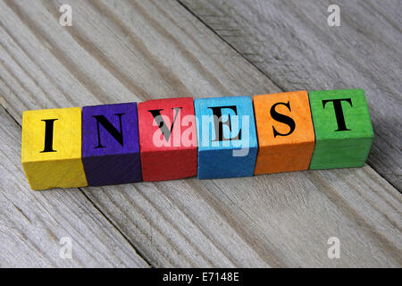 word invest on colorful wooden cubes - Stock Photo