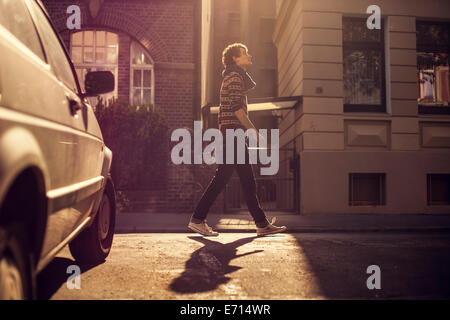 Germany, Hannover, Young man strolling in the city - Stock Photo