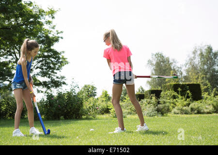 Two girls playing hockey on a meadow - Stock Photo