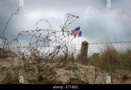 France, Lower Normandy, Manche, Sainte Marie du Mont, Utah Beach, Barbed wire fence and French and US flag - Stock Photo