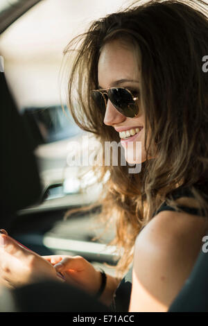 Portrait of smiling teenage girl with sunglasses sitting in a car using her smartphone - Stock Photo