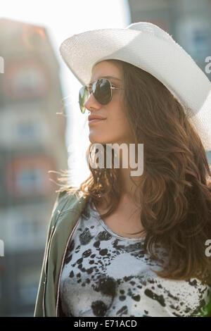 Portrait of teenage girl wearing sunglasses and white hat - Stock Photo