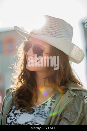 Portrait of smiling teenage girl wearing sunglasses and white hat - Stock Photo