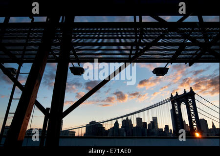 View of Manhattan Bridge at sunset from Brooklyn rooftop, framed by billboard structure in foreground. - Stock Photo