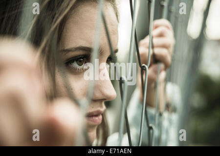 Teenage girl looking through a wire fence - Stock Photo