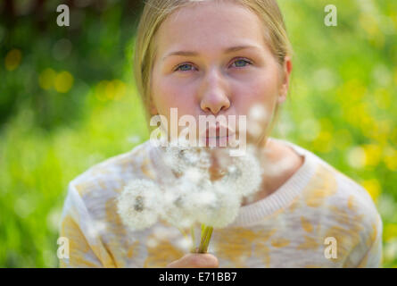 Portrait of teenage girl blowing blowballs on a flower meadow - Stock Photo