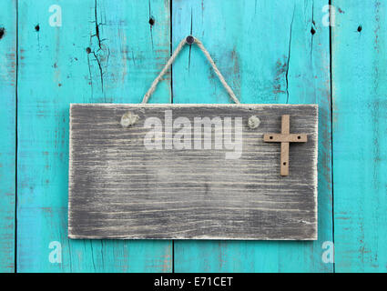 Weathered blank sign with wooden cross hanging on antique teal blue rustic wood door - Stock Photo