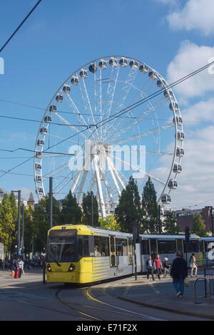 Metrolink tram passing through Piccadilly, Manchester, with the Manchester Eye in the background. - Stock Photo