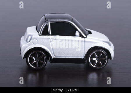 Side view of white, toy, small car on wooden table. - Stock Photo