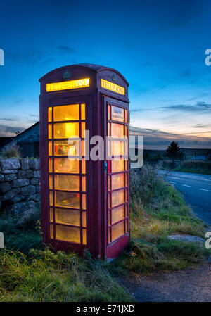 Old red phone box at dusk on a country road in Dartmoor, Devon - Stock Photo