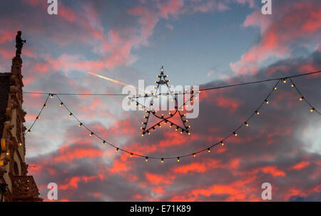 Christmas Star in front of pink dusk clouds at the Christmas market in Colmar, France - Stock Photo