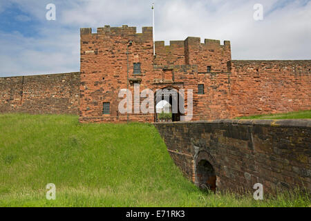 Historic Carlisle castle with imposing red sandstone walls, entrance with portcullis,and grassy moat under blue - Stock Photo