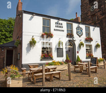 Old English pub with white painted facade, colourful flowers in window boxes, and outdoor dining area at village - Stock Photo