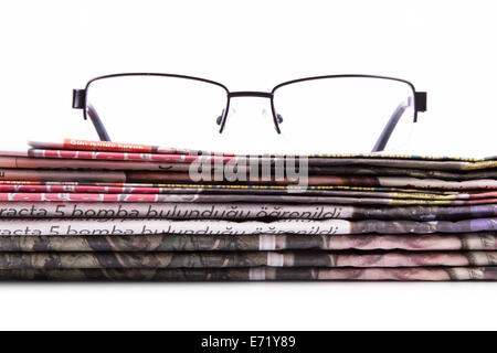 Stack of newspapers and eye glasses, isolated on white background. - Stock Photo