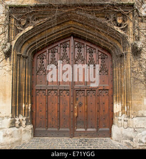 Spectacular rich brown double wooden doors with intricate carving and decorative arched stone surrounds of historic - Stock Photo