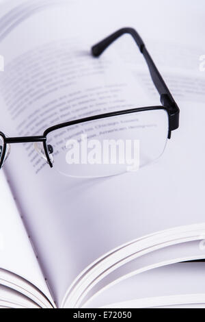 Eyeglasses on opened book, isolated on white background. - Stock Photo
