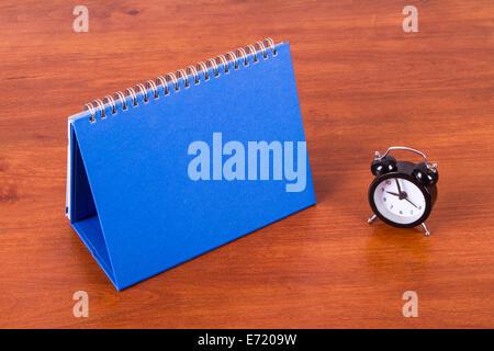 Desk calendar mock up with alarm clock on table. - Stock Photo