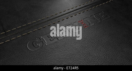 A concept image showing a regular stitched sheet of black leather with an embossed stamp reading genuine but the - Stock Photo