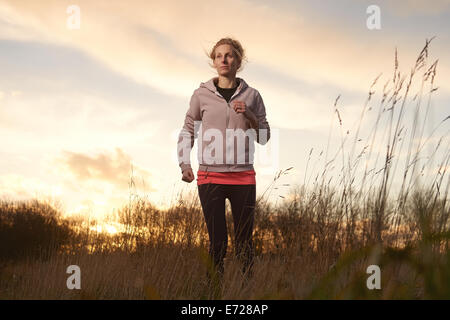 A woman in her 30's running in a field of long grass as the sun sets - Stock Photo