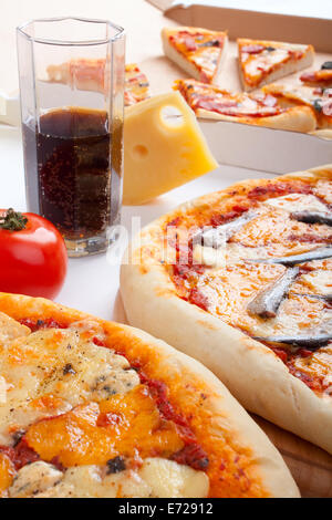 three different kinds of pizza and a glass of cola - Stock Photo