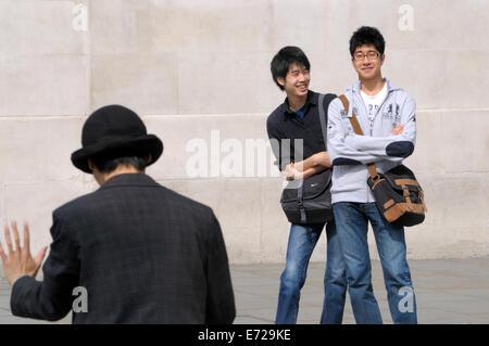 London, England, UK. Japanese tourists watching a mime artist in Trafalgar Square - Stock Photo