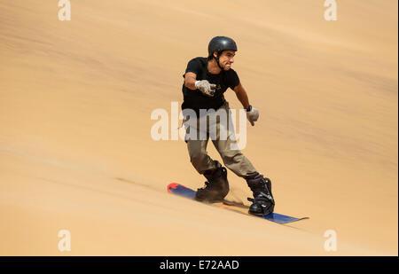 Sand boarding in the dunes of the Namib Desert, near Swakopmund, Namibia - Stock Photo
