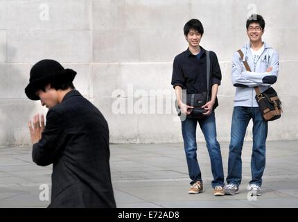 London, England, UK. Tourists watching a mime artist in Trafalgar Square - Stock Photo