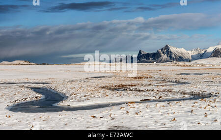 A frozen stream meandering through the snow at Fredvang on the Lofoten islands - Stock Photo