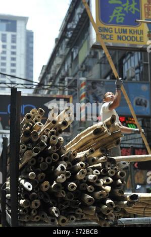 Bamboo poles, awaiting use in construction of scaffolding, Kowloon, Hong Kong, China - Stock Photo