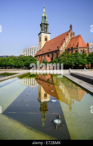 Germany, Berlin, Marienkirche  St Marys Church dating from the 13th Century  reflected in fountain pool. - Stock Photo