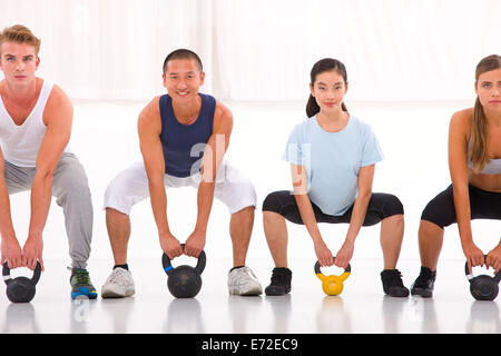 Multiethnic group of people doing kettlebell crossfit exercise - Stock Photo