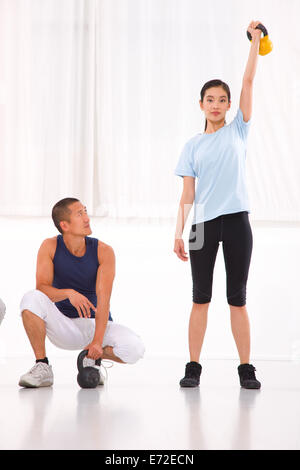 Asian man looking woman doing kettle bell crossfit exercise - Stock Photo