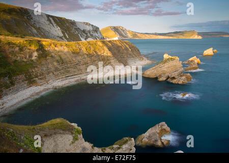 Setting sunlight over Mupe Bay along the Jurassic Coast near Lulworth, Dorset, England - Stock Photo