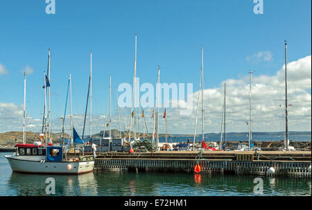 Moored boats at a jetty in the southern port on the island of Stora Dyrön, Bohuslän, Västra Götaland County, Sweden. - Stock Photo