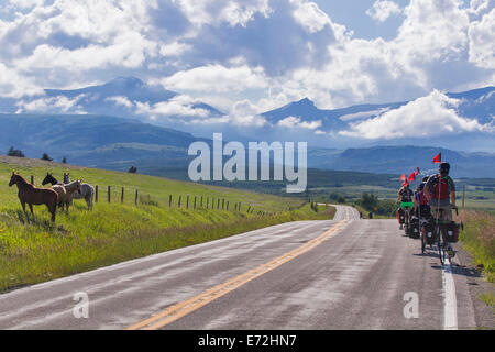 Teenagers bicycle touring with Apogee Adventures on Highway 89 on the Blackfeet Indian Reservation, Montana, USA. - Stock Photo