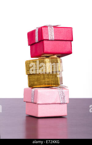 Three colorful gift boxes in row on wooden table, isolated on white background. - Stock Photo