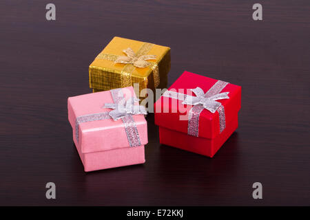 Three colorful gift boxes on wooden table. - Stock Photo
