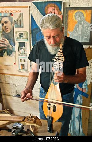 Mr. Manolis Haroulis, artist and handicraftsman in his workshop at Exo Lakonia village, Lasithi, Crete island, Greece - Stock Photo