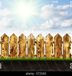 Garden wooden fence on the grass on a sunny day - Stock Photo