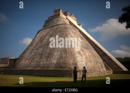 A guide speaks with a tourist in front of the Pyramid of the Magician or the Temple of the Magician in the Mayan - Stock Photo